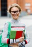 Muchacha sonriente con los auriculares en la calle delante del edificio Fotografía de archivo
