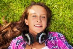Muchacha sonriente con los auriculares que ponen en hierba verde Fotografía de archivo