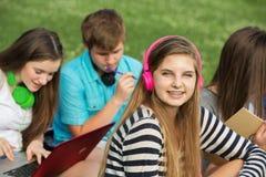 Muchacha sonriente con los auriculares rosados Imagenes de archivo