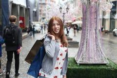 Muchacha sonriente con los bolsos de compras Imagenes de archivo