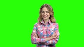Muchacha sonriente con los brazos cruzados en la pantalla verde almacen de metraje de vídeo