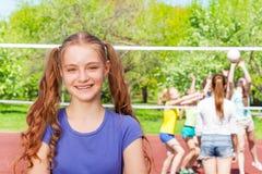Muchacha sonriente con los compañeros de clase que juegan a voleibol Imagen de archivo libre de regalías