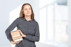 Muchacha sonriente con los libros apilados Imagen de archivo libre de regalías