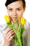 Muchacha sonriente con los tulipanes Fotos de archivo