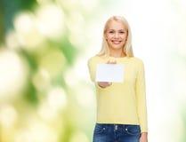Muchacha sonriente con negocio en blanco o la tarjeta de presentación Imágenes de archivo libres de regalías