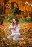 Muchacha sonriente con PC de la tableta en el paisaje del otoño, al aire libre Imagen de archivo