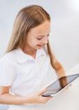 Muchacha sonriente con PC de la tableta en la escuela Foto de archivo libre de regalías
