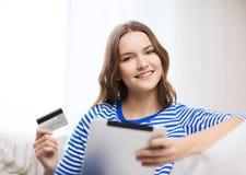 Muchacha sonriente con PC de la tableta y la tarjeta de crédito Imagen de archivo libre de regalías