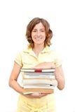 Muchacha sonriente con pegado de libros sobre blanco Foto de archivo libre de regalías