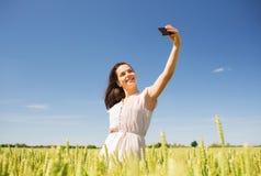 Muchacha sonriente con smartphone en campo de cereal Fotografía de archivo