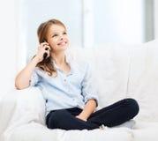 Muchacha sonriente con smartphone en casa Imagenes de archivo