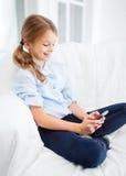Muchacha sonriente con smartphone en casa Imagen de archivo
