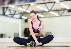 Muchacha sonriente con smartphone y auriculares en gimnasio Foto de archivo