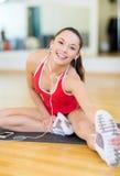 Muchacha sonriente con smartphone y auriculares en gimnasio Fotografía de archivo