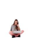 Muchacha sonriente con su mano cerca de la cara que se sienta en el piso con c Imagen de archivo
