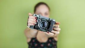 Muchacha sonriente con tomar retro de la cámara del vintage Imágenes de archivo libres de regalías
