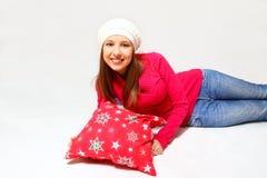 Muchacha sonriente con un casquillo y una mentira de la almohada   Fotografía de archivo