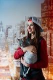 Muchacha sonriente con un gato en manos Foto vertical Imagen de archivo