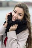 Muchacha sonriente con un maquillaje natural que mira la cámara Muchacha en una capa negra, una bufanda y un vestido rojo contra  Imágenes de archivo libres de regalías