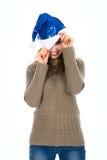 Muchacha sonriente con un ojo que mira a escondidas de los sombreros de Papá Noel Imagen de archivo libre de regalías