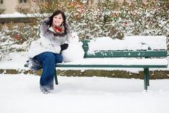 Muchacha sonriente con un pequeño muñeco de nieve Fotos de archivo libres de regalías