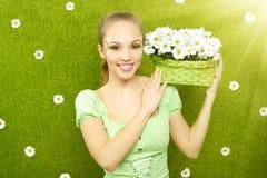 Muchacha sonriente con una cesta de flores Foto de archivo libre de regalías