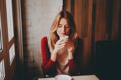 Muchacha sonriente con una taza de latte Foto de archivo