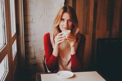 Muchacha sonriente con una taza de latte Fotos de archivo libres de regalías