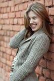 Muchacha sonriente contra la pared Imagenes de archivo