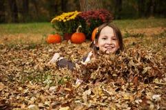 Muchacha sonriente cubierta en hojas de otoño de la caída Foto de archivo libre de regalías