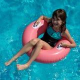 Muchacha sonriente de Beautigul que se sienta en el tubo rosado grande de la nadada en Imágenes de archivo libres de regalías
