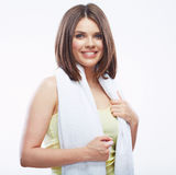 Muchacha sonriente de la aptitud que sostiene la toalla en el fondo blanco Imagen de archivo libre de regalías