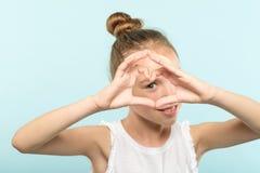 Muchacha sonriente de la emoción del amor que mira la mano de la forma del corazón imagenes de archivo