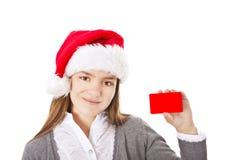 Muchacha sonriente de la Navidad que sostiene la tarjeta vacía roja con el lugar para el tex Imagen de archivo libre de regalías