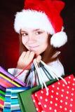Muchacha sonriente de la Navidad que sostiene los actuales bolsos Foto de archivo libre de regalías