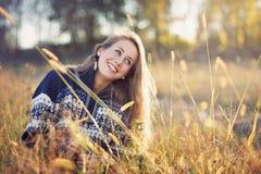 Muchacha sonriente de los ojos azules en un campo foto de archivo