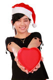 Muchacha sonriente de Navidad que da el corazón Foto de archivo libre de regalías