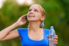 Muchacha sonriente del adolescente con la botella Foto de archivo libre de regalías