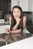 Muchacha sonriente del adolescente con la manzana en cocina Fotos de archivo libres de regalías