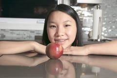 Muchacha sonriente del adolescente con la manzana en cocina Fotografía de archivo libre de regalías