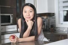 Muchacha sonriente del adolescente con la manzana en cocina Foto de archivo libre de regalías