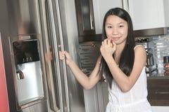 Muchacha sonriente del adolescente con la manzana en cocina Fotografía de archivo