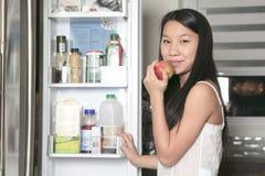 Muchacha sonriente del adolescente con la manzana en cocina Imagenes de archivo