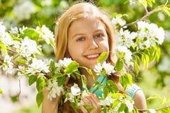 Muchacha sonriente del adolescente con las flores en el peral Fotografía de archivo