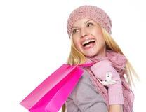 Muchacha sonriente del adolescente en sombrero y bufanda del invierno con el bolso de compras Foto de archivo libre de regalías