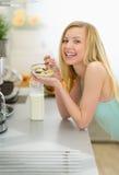Muchacha sonriente del adolescente que come el desayuno en cocina Fotos de archivo libres de regalías