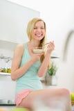 Muchacha sonriente del adolescente que come escamas con leche Imagen de archivo