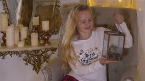 Muchacha sonriente del adolescente que considera la linterna decorativa de la Navidad la víspera del día de fiesta almacen de video