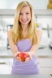 Muchacha sonriente del adolescente que da la manzana en cocina Imágenes de archivo libres de regalías