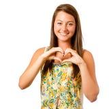 Muchacha sonriente del adolescente que hace dimensión de una variable del corazón Imagen de archivo